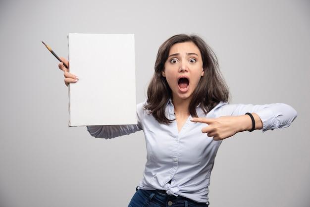 Mulher gritando, apontando para uma tela vazia.
