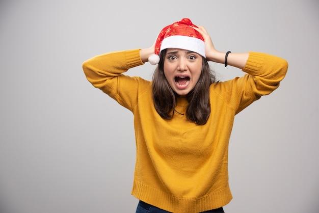 Mulher gritando com chapéu de papai noel vermelho posando sobre uma parede branca.