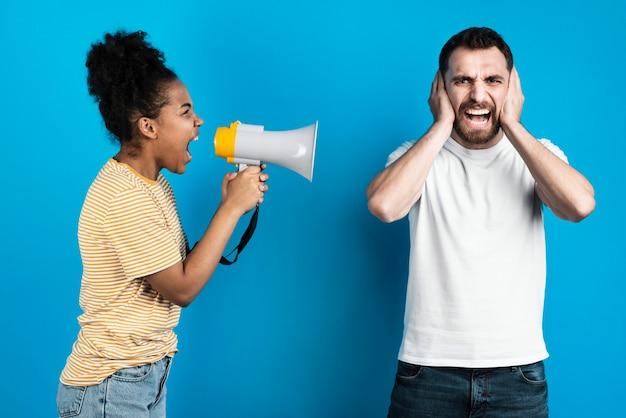 Mulher gritando com homem através de megafone