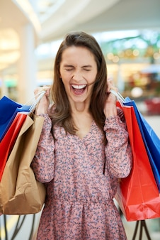 Mulher gritando com sacolas de compras