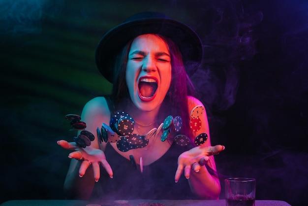 Mulher gritando e jogando pôquer com luzes de néon vermelhas e azuis em fundo preto