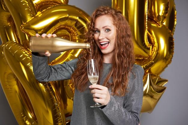 Mulher gritando, servindo champanhe na foto do estúdio