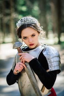 Mulher guerreira armada medieval em armadura posando em pé no fundo da floresta e o pôr do sol.
