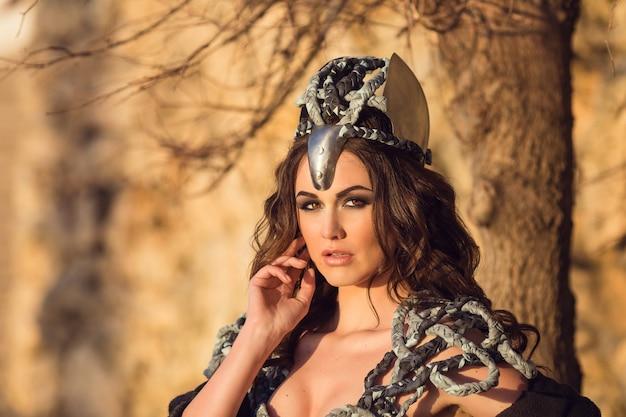 Mulher guerreira. ideia de fantasia de moda. retrato de uma bela senhora guerreira, garota de cabelos escuros em um vestido cinza.