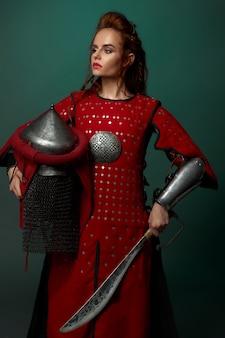 Mulher guerreira posando com punhal, capacete na mão.