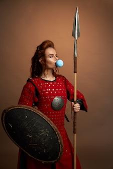 Mulher guerreira soprando chiclete azul grande.