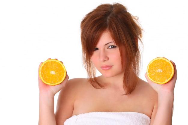 Mulher haelthy jovem sorridente, segurando a laranja na mão