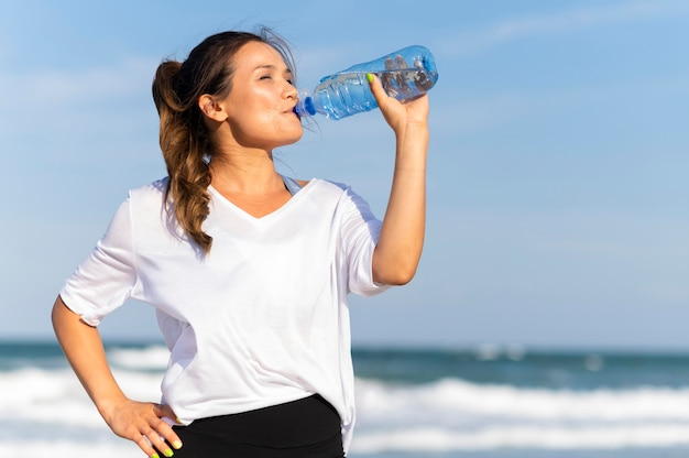 Mulher hidratada na praia enquanto faz exercícios
