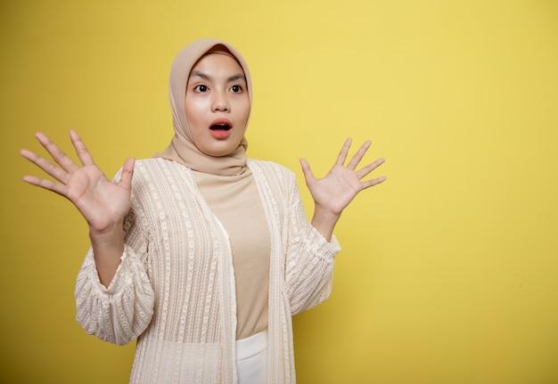Mulher hijab com expressão chocada, olhando algo isolado em uma parede amarela