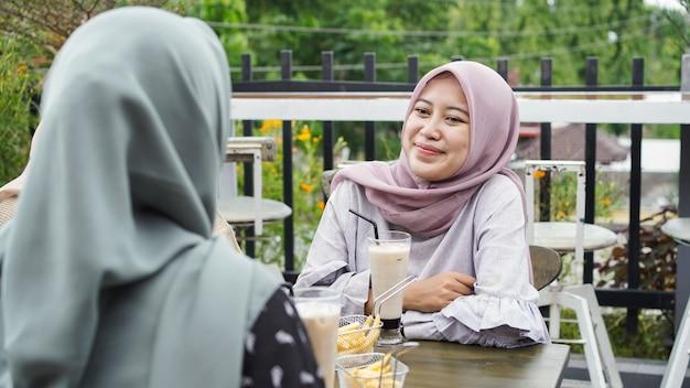 Mulher hijab de grupo asiático sorrindo em um café com um amigo
