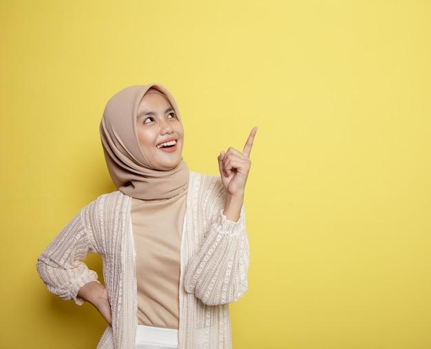 Mulher hijab feliz apontando para o espaço em branco isolado na parede amarela