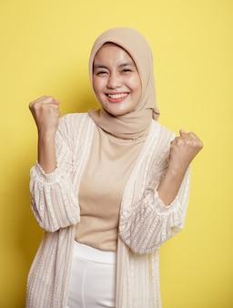 Mulher hijab muito animada olhando para a câmera isolada em uma parede amarela
