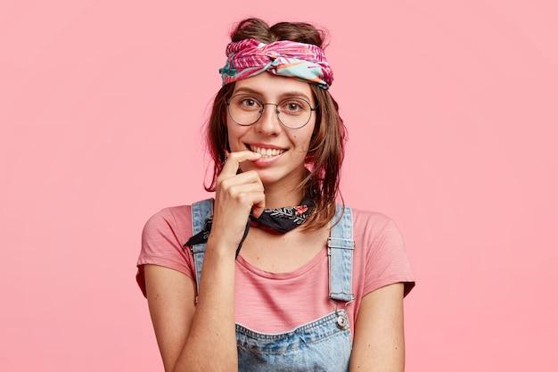 Mulher hippie satisfeita e encantada com sorriso gentil, encontra-se com um amigo, tem uma conversa agradável, usa bandana estilosa na cabeça, isolada sobre parede rosa