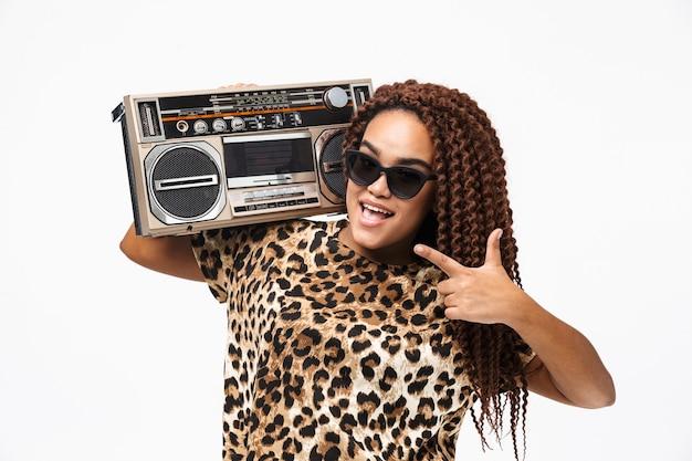 Mulher hipster sorrindo e segurando uma caixa de som vintage com fita cassete no ombro, isolada contra uma parede branca