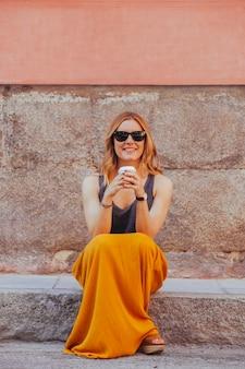 Mulher hipster tomando um café para ir na rua
