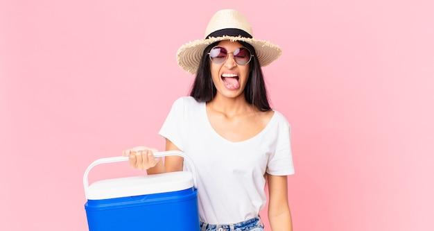 Mulher hispânica bonita com atitude alegre e rebelde, brincando e mostrando a língua com uma geladeira portátil de piquenique