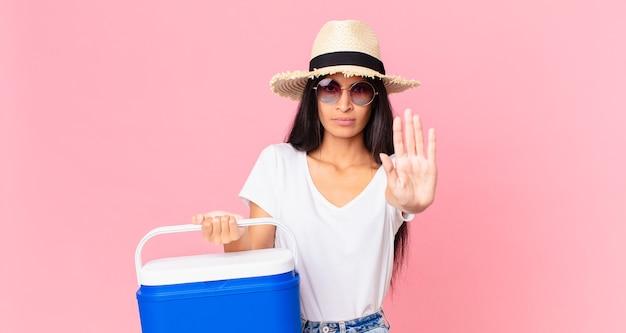 Mulher hispânica bonita com expressão séria, mostrando a palma da mão aberta, fazendo gesto de pare com uma geladeira portátil de piquenique