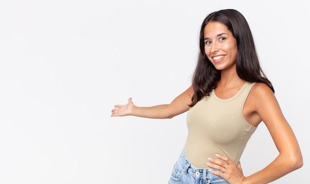 Mulher hispânica bonita e magra se sentindo feliz e alegre, convidando você para entrar com um gesto amigável