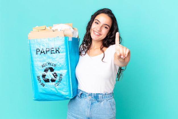 Mulher hispânica bonita sorrindo com orgulho e confiança, alcançando o primeiro lugar e segurando uma sacola de papel reciclado