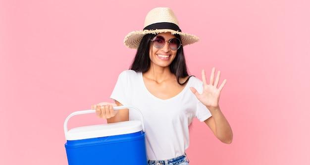 Mulher hispânica bonita sorrindo e parecendo amigável, mostrando o número cinco com uma geladeira portátil de piquenique