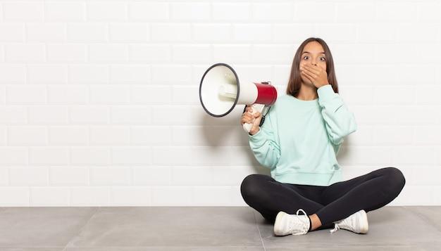 Mulher hispânica cobrindo a boca com as mãos com uma expressão chocada e surpresa, mantendo um segredo ou dizendo oops