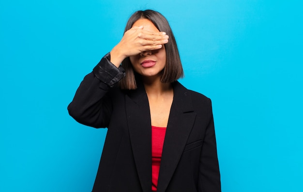 Mulher hispânica cobrindo os olhos com uma mão sentindo-se assustada ou ansiosa, imaginando ou esperando cegamente por uma surpresa