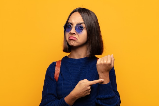 Mulher hispânica com aparência impaciente e zangada, apontando para o relógio, pedindo pontualidade, quer ser pontual