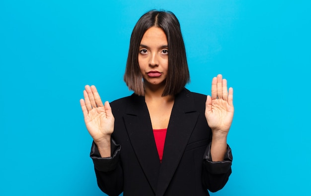 Mulher hispânica com aparência séria, infeliz, irritada e descontente, proibindo a entrada ou dizendo para com as palmas das mãos abertas