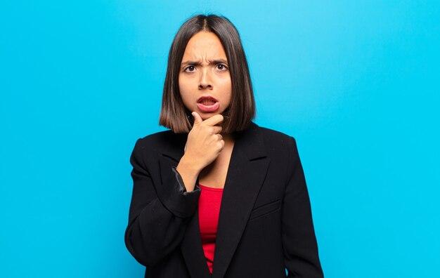 Mulher hispânica com boca e olhos bem abertos e mão no queixo, sentindo-se desagradavelmente chocada, dizendo o quê ou uau