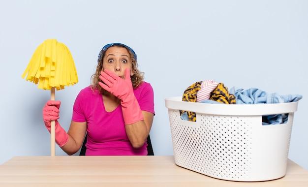 Mulher hispânica de meia-idade cobrindo a boca com as mãos com uma expressão chocada e surpresa, mantendo um segredo ou dizendo oops