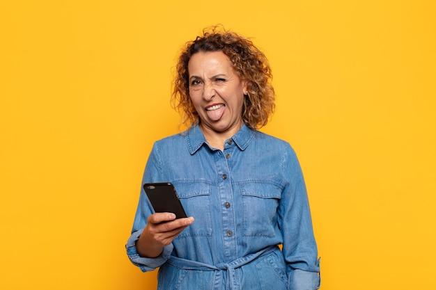 Mulher hispânica de meia-idade com atitude alegre, despreocupada e rebelde, brincando e mostrando a língua, se divertindo