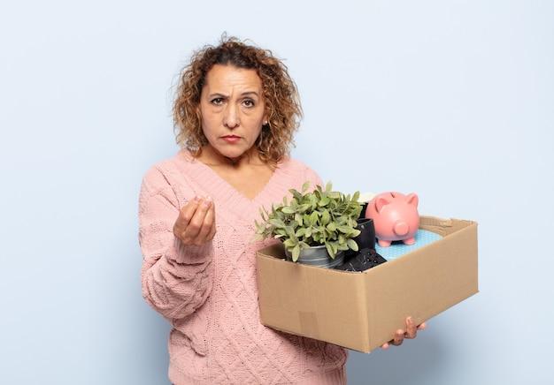 Mulher hispânica de meia idade fazendo capice ou gesto de dinheiro, dizendo para você pagar suas dívidas!