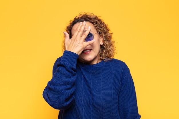 Mulher hispânica de meia-idade parecendo chocada, assustada ou apavorada, cobrindo o rosto com a mão e espiando por entre os dedos