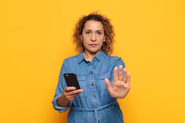 Mulher hispânica de meia-idade parecendo séria, severa, descontente e irritada, mostrando a palma da mão aberta fazendo gesto de pare