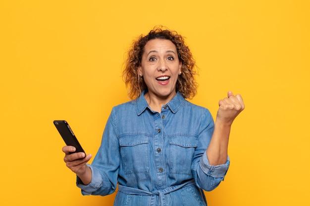 Mulher hispânica de meia-idade se sentindo chocada, animada e feliz, rindo e comemorando o sucesso, dizendo uau!