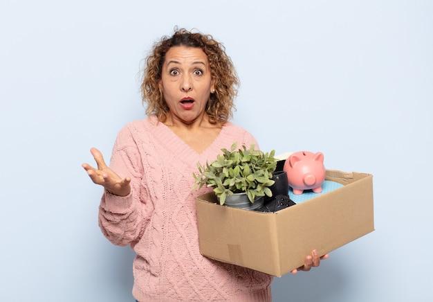 Mulher hispânica de meia-idade se sentindo extremamente chocada e surpresa, ansiosa e em pânico, com uma aparência estressada e horrorizada