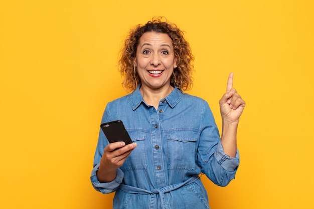 Mulher hispânica de meia-idade se sentindo um gênio feliz e animado depois de realizar uma ideia, levantando o dedo alegremente, eureka!