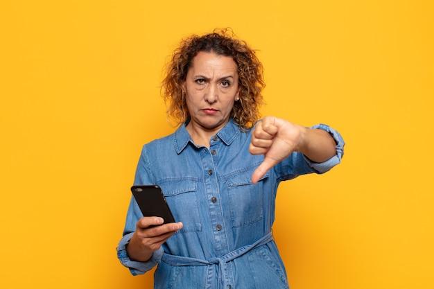 Mulher hispânica de meia-idade se sentindo zangada, irritada, irritada, decepcionada ou descontente, mostrando o polegar para baixo com um olhar sério
