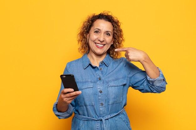 Mulher hispânica de meia-idade sorrindo com confiança apontando para o próprio sorriso largo