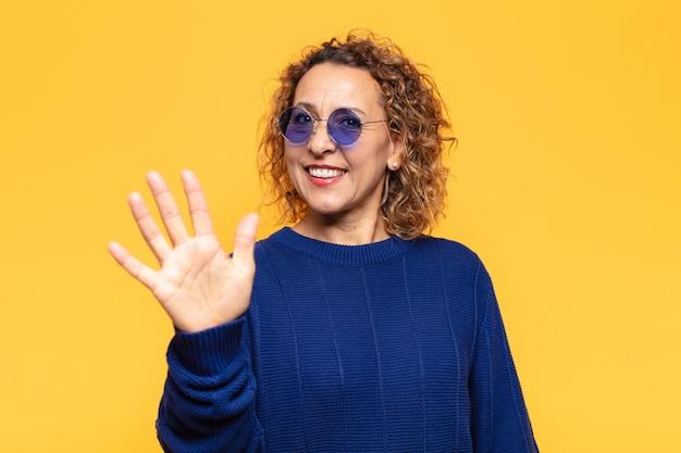 Mulher hispânica de meia idade sorrindo e parecendo amigável, mostrando o número cinco ou quinto com a mão para a frente, em contagem regressiva