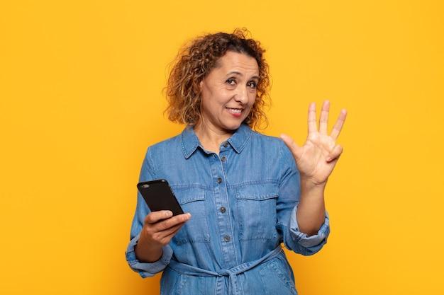 Mulher hispânica de meia idade sorrindo e parecendo amigável, mostrando o número quatro ou o quarto com a mão para a frente, em contagem regressiva