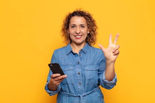 Mulher hispânica de meia idade sorrindo e parecendo amigável, mostrando o número três ou terceiro com a mão para a frente, em contagem regressiva