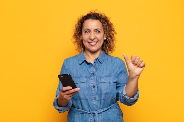 Mulher hispânica de meia idade sorrindo e parecendo amigável, mostrando o número um ou primeiro com a mão para a frente, em contagem regressiva
