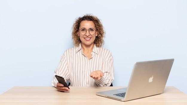 Mulher hispânica de meia-idade sorrindo feliz com um olhar amigável, confiante e positivo, oferecendo e mostrando um objeto ou conceito