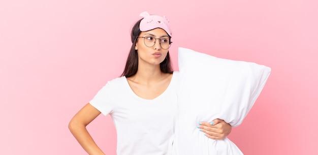 Mulher hispânica de pijama encolhendo os ombros, sentindo-se confusa e insegura e segurando um travesseiro