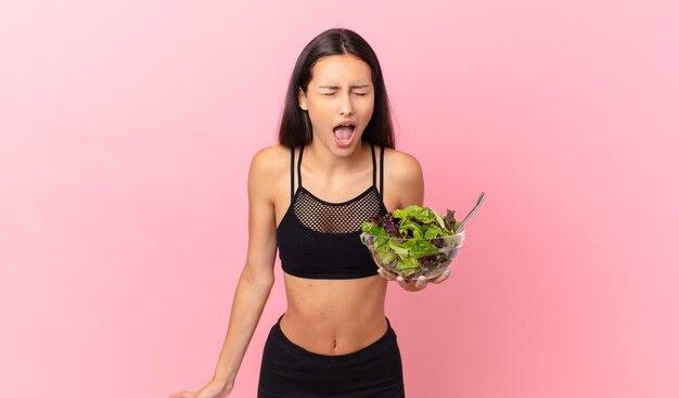 Mulher hispânica em boa forma gritando agressivamente, parecendo muito zangada e segurando uma salada