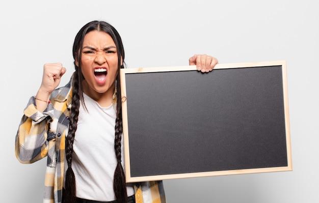 Mulher hispânica gritando agressivamente com uma expressão de raiva ou com os punhos cerrados celebrando o sucesso