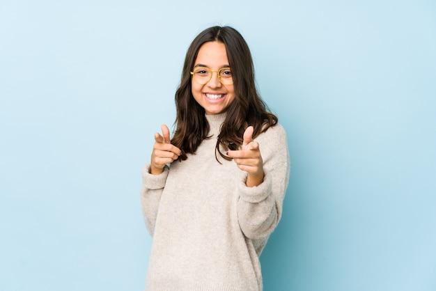 Mulher hispânica jovem de raça mista isolada apontando para a frente com os dedos.