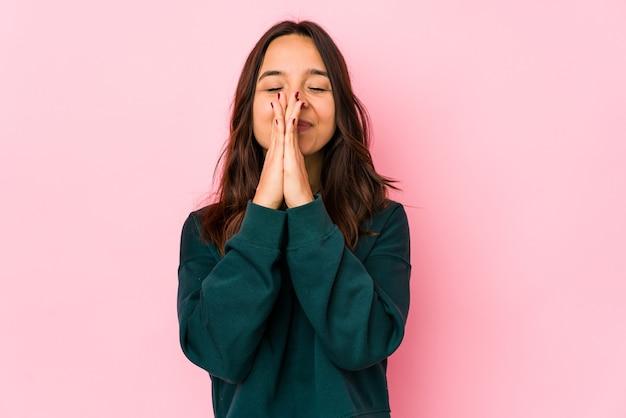 Mulher hispânica jovem de raça mista isolada de mãos dadas orando perto da boca, sente-se confiante.