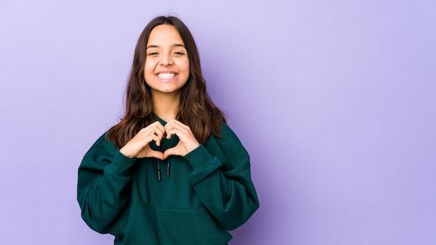 Mulher hispânica jovem de raça mista isolada sorrindo e mostrando uma forma de coração com as mãos.